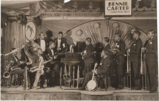 "Original photograph; of 11-piece band posed on the stage of Savoy Ballroom beneath the sign ""Bennie Carter and his Savoy Playboys"" Benny Carter."